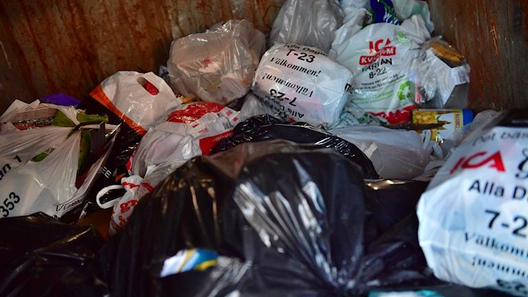 Soppåsar ligger i en container.
