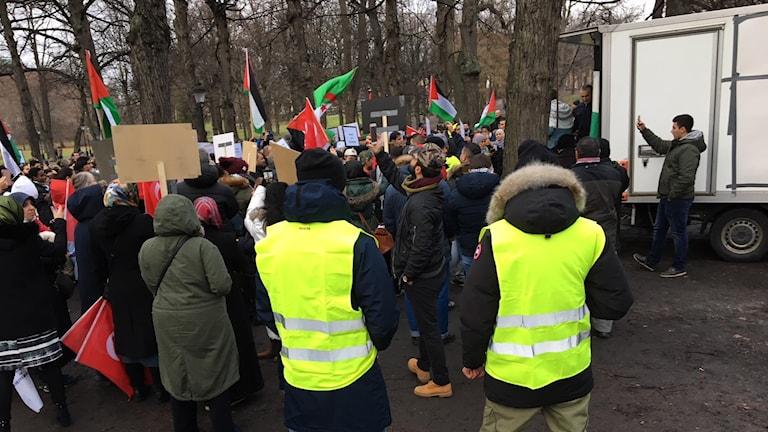 En folksamling med ett hundratal personer, som viftar med flaggor, och håller upp plakat.