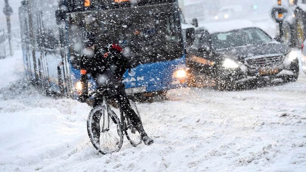 En cyklist på på en snöfylld gata vid Slussen i centrala Stockholm