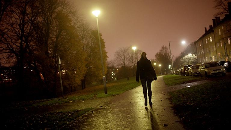En kvinna går på en gångväg en mörk kväll Foto: Stian Lysberg Solum / TT
