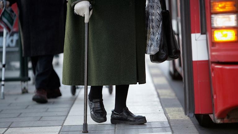En äldre kvinna med käpp är på väg att kliva på en röd SL-buss. Foto: Fredrik Sandberg/TT