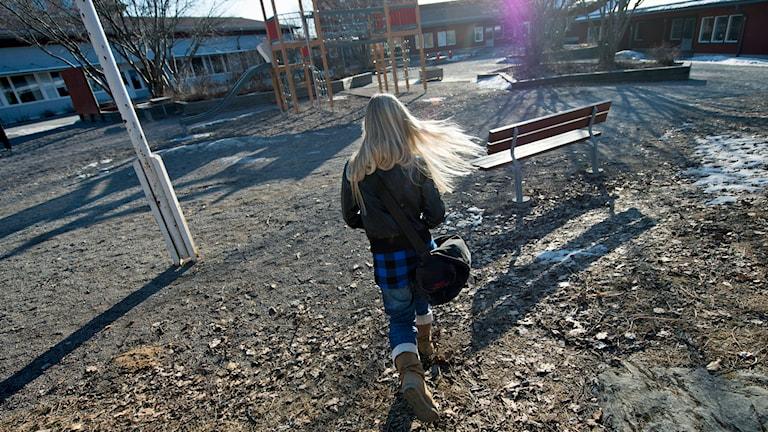En ensam flicka går över en skolgård med skolväskan på axeln Foto: Fredrik Sandberg /TT.