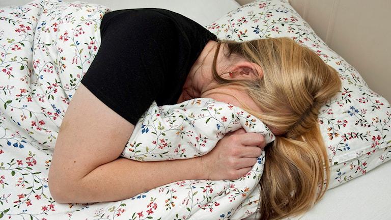 En tjej ligger i en säng och gömmer ansiktet under täcket. Foto Jonas Ekströmer /TT.