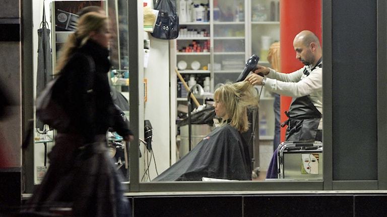 Skyltfönster kvällstid. Frisör som klipper en kund. Foto: Anders Wiklund /TT.
