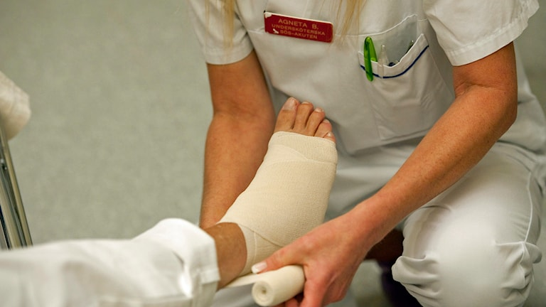En undersköterska på akuten på Södersjukhuset lindar foten på en patient Foto: Leif R Jansson /TT.