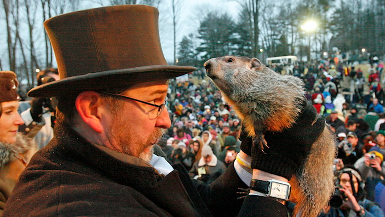 Punxsutawney Phil, right, is held by Ben Hughes after emerging from his burrow on Gobblers Knob in Punxsutawney, Pa., to see his shadow and forecast six more weeks of winter weather Tuesday, Feb. 2, 2010. (AP Photo/Gene J. Puskar)
