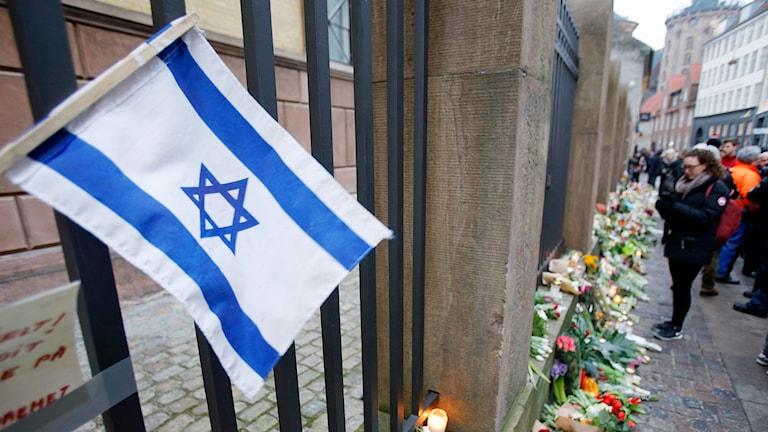 En israelisk flagga utanför synagogan i Köpenhamn där en person sköts ihjäl. Foto: AP Photo/Michael Probst/TT.