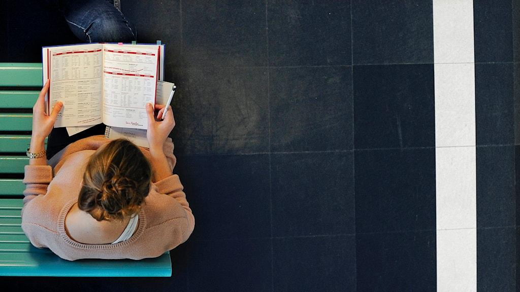 En kvinnlig student vid Stockholms universitet sitter lutad över sina böcker. Foto: Anders Wiklund /TT.