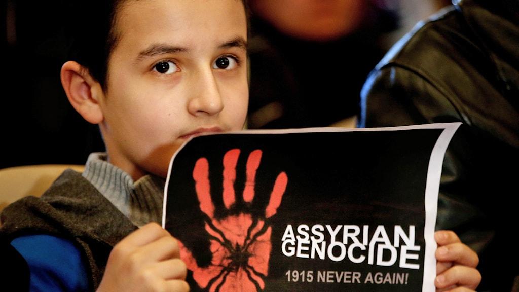 En pojke håller en skylt med texten uppmaningen att stoppa folkmordet av assyrierna. Foto: Hussein Malla /AP Photo/TT.