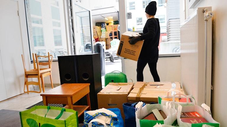 Flyttkartonger och möbler bärs ut till en flyttbil.