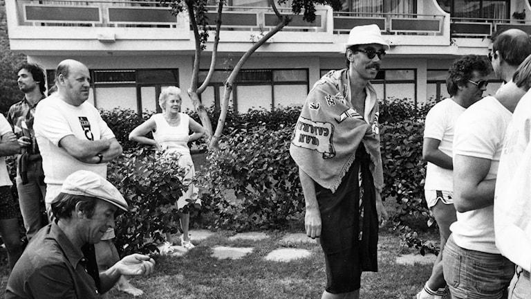Inspelning av filmen 'Sällskapsresan' i San Agustin på Gran Canaria. Regissören och huvudrollsinnehavaren Lasse Åberg (med solglasögon) kopplar av under en paus. Arkivfoto: Gunnar Lantz / TT.