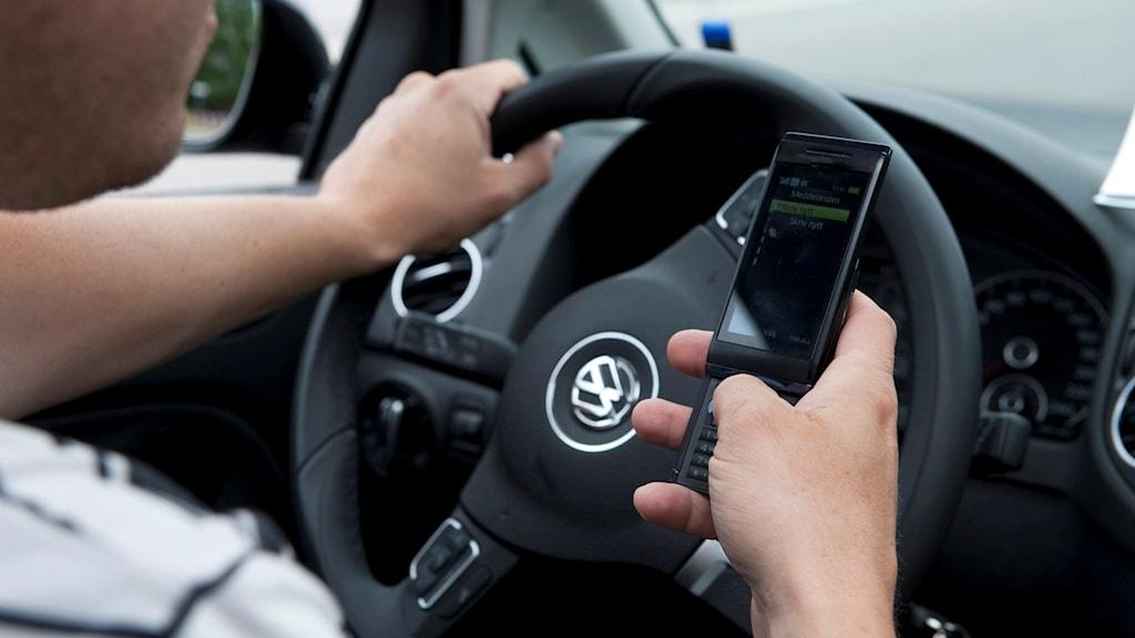 En bilförare skickar SMS med mobilen under körning. Foto: Bertil Ericson/TT