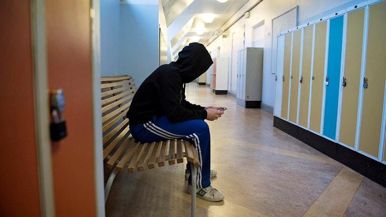 En elev i huvatröja sitter på en bänk i en korridor i Sofia skola. Foto: Jessica Gow / TT.