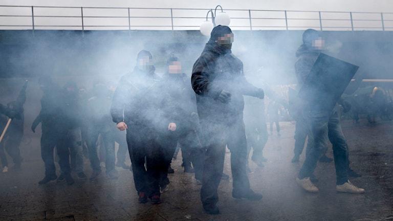 Mörkklädda män i rök framför viadukt