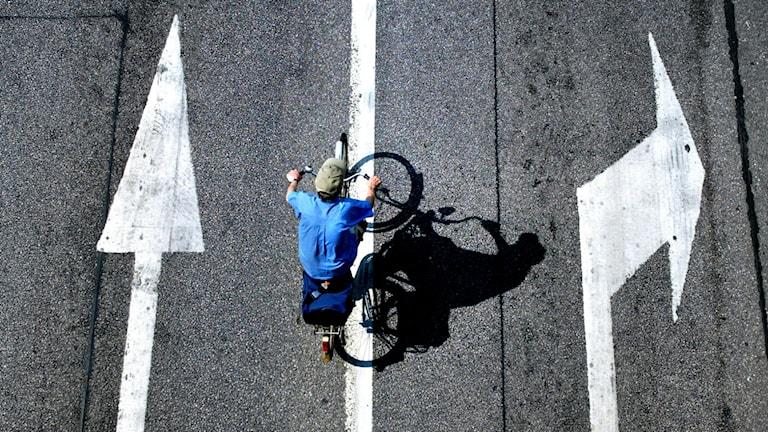 En cyklist tar sig fram mellan två filer på Hamngatan i Stockholm. Foto Jessica Gow/TT