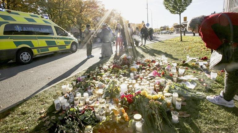 En kvinna lägger ner blommor utanför Kronan skolan i Trollhättan på fredagen. I bakgrunden kör en ambulans iväg en person som skadats lindrigt då han blev påkörd i trängseln utanför skolan. Två personer avled av sina skador när en knivman attackerade elever och personal på Kronan skolan i Trollhättan under torsdagen. Foto: Björn Larsson Rosvall / TT
