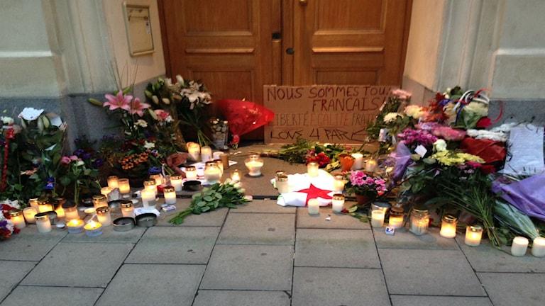 Blommor och ljus utanför den Franska ambassaden.