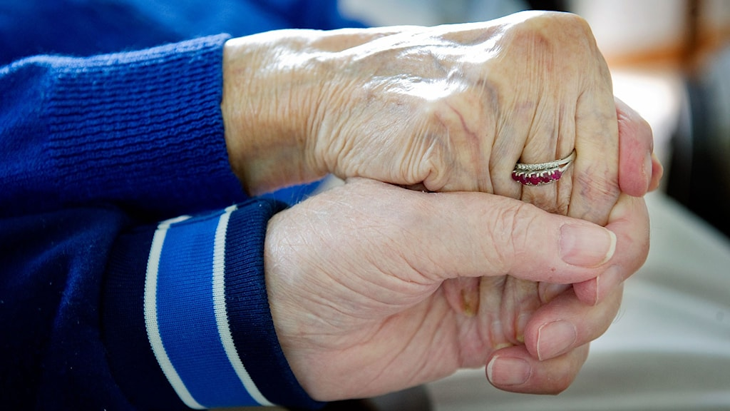 Äldre par håller varann i handen.