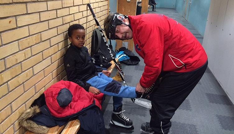 Ove Eriksson hjälper barnen att snöra skidskorna. Foto: Lasse Persson/Sveriges Radio.