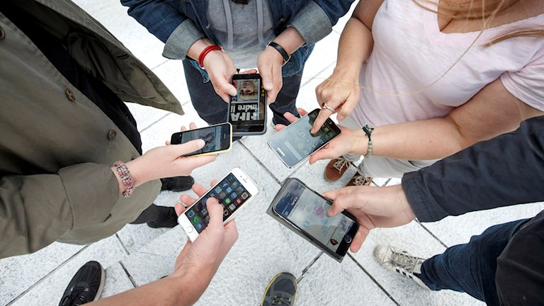 5 människor står i en cirkel med mobiltelefoner