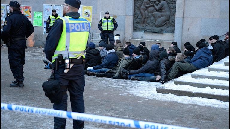 Demonstranter från Nazistiska Svenska motståndsrörelsen bevakade av polisen på Medborgarplatsen.