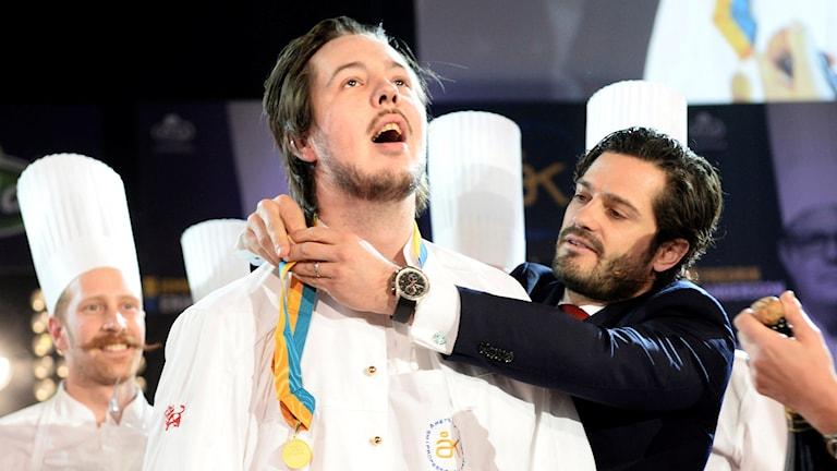 En kock får medalj av prins Carl Philip