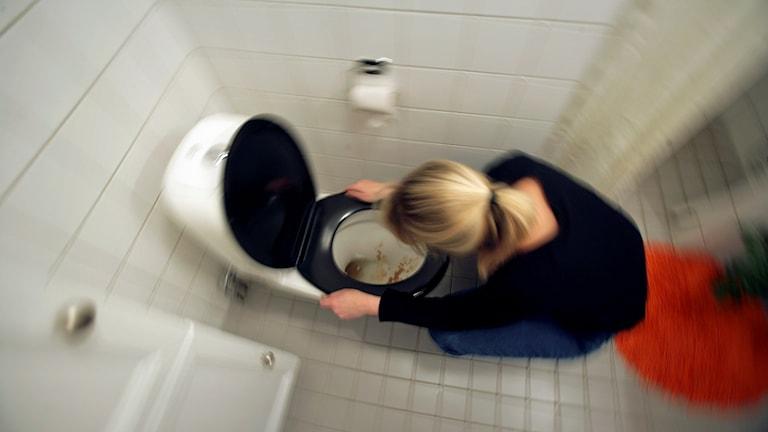 Kvinna som sitter hukad över en toalett