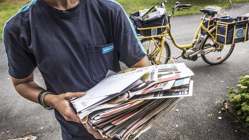 En brevbärare med händerna fulla av reklam. En postcykel i bakgrunden.