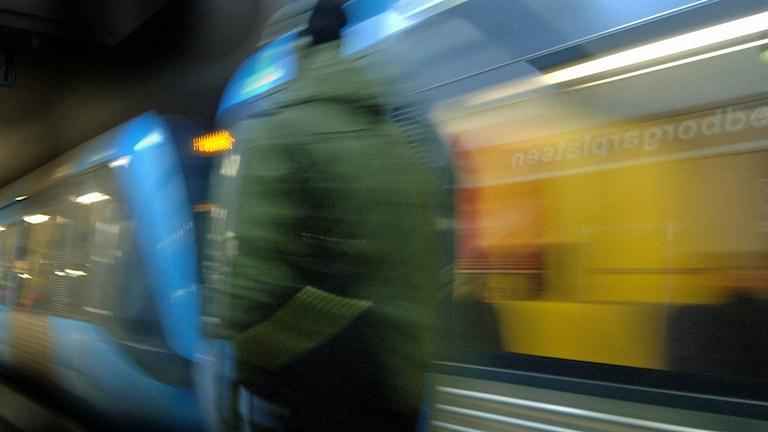 Man med grön jacka går brevid ett framrusande tunnelbanetåg