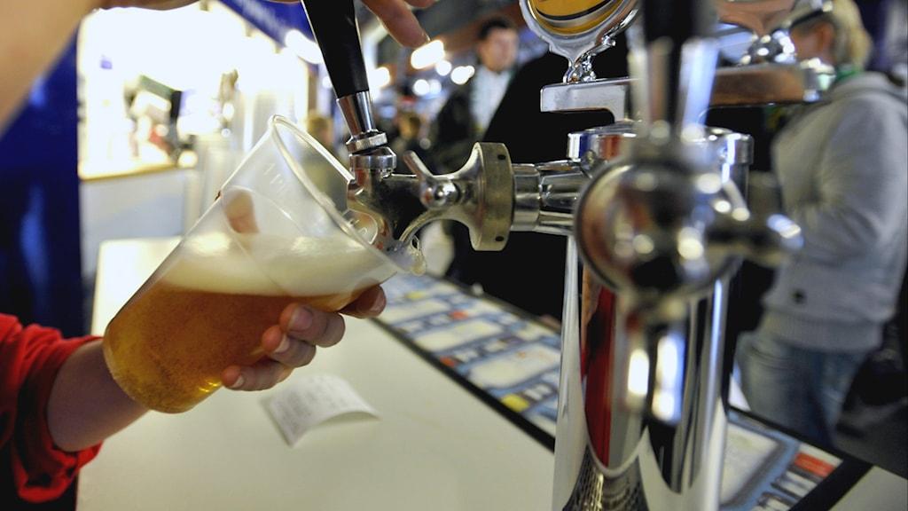 Häller upp öl.