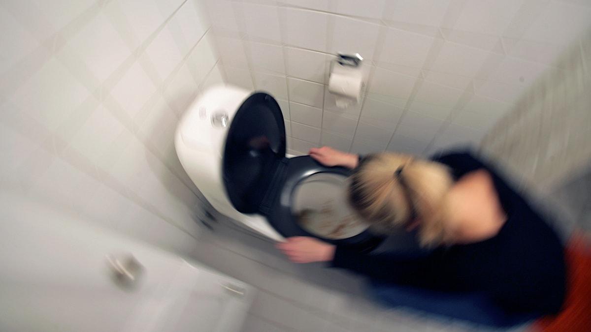 Kvinna som kräks i en toalett