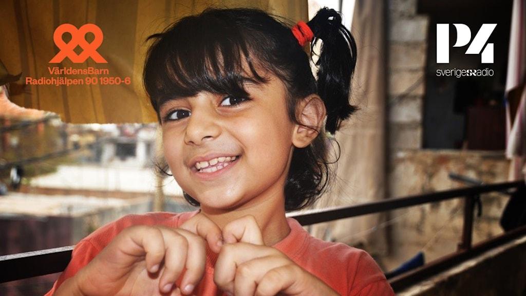 En flicka som ler och formar ett hjärta av sina händer.