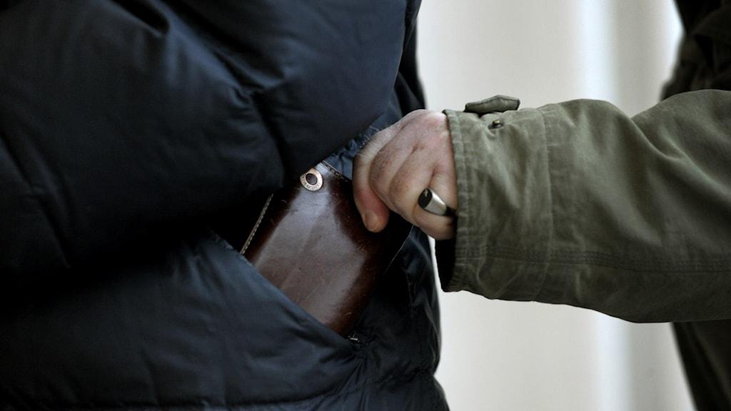 En ficktjuv som plockar upp en plånbok från någon annans ficka.