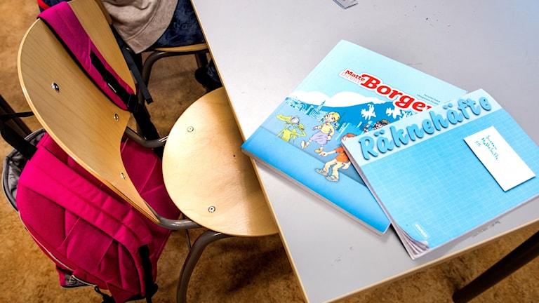Skolböcker på en bänk.