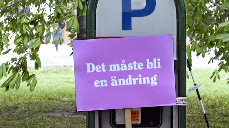 Parkeringsautomat med en skylt påklistard där det står, Det måste bli ändring