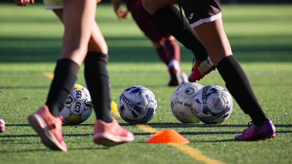 Barnben med fotbollsstrumpor trixar med fotbollar på fotbollsplan.