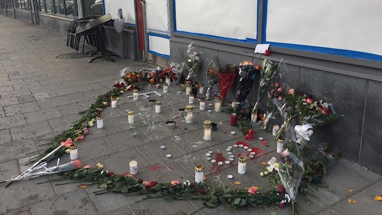 De döda hedras med blommor och ljus utanför caféet.