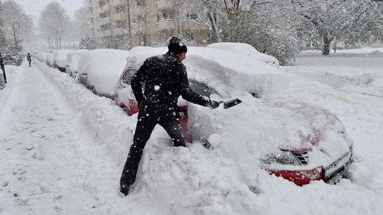 Snöväder i Stockholm. Man borstar bort snön.