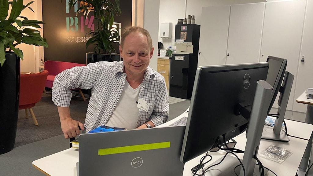 En man i mönstrad vit skjorta sitter vid en dator.