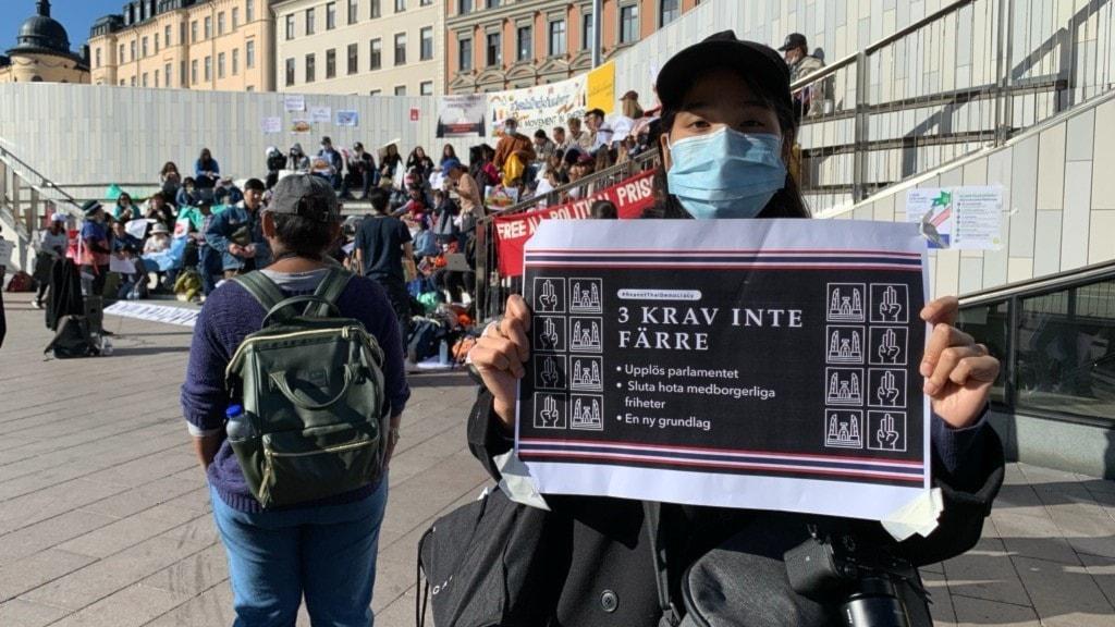 """Demonstranten Nina Suviporn håller upp en skylt där det står """"Tre krav inte färre""""."""