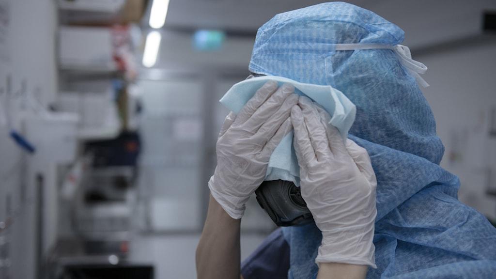 Vårdpersonal i utrustning, munskydd och hätta, tarkar av ansiktet med servett.