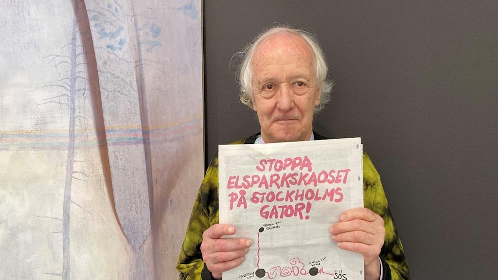 """En man med vitt hår håller upp en tidningssida med en designad annons där det står """"Stoppa elsparkskaoset på Stockholms gator."""""""