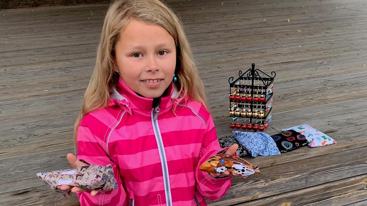 Åttaåriga Amanda Tönne sitter utomhus med saker hon ska sälja för Världens barn.