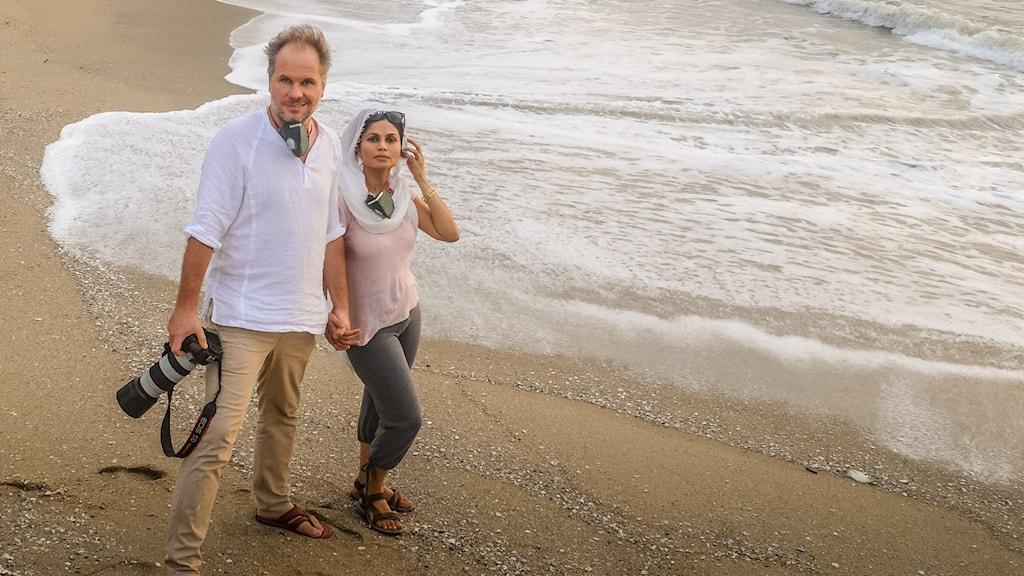 Mattias Löw och Reshma Mansuri Löw står tillsammans på en strand precis intill vattnet.