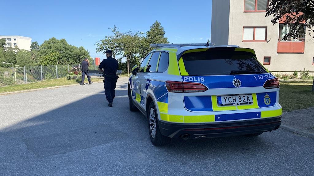 Polisbil i förgrund två poliser i bakgrunden