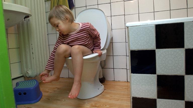 Barn på toalettstol