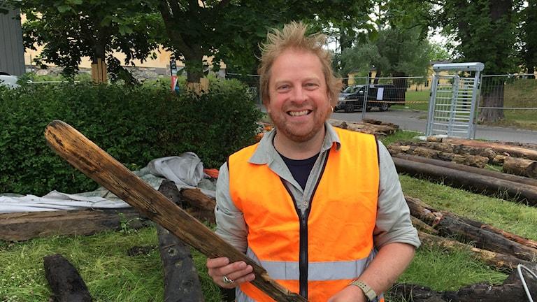 Jim Hansson är marinarkeolog och visar upp ett klappträ som hittats i samband med vrakdelarna.