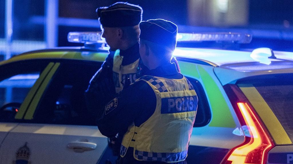 Två poliser i silhuett vid en polisbil med blåljus.