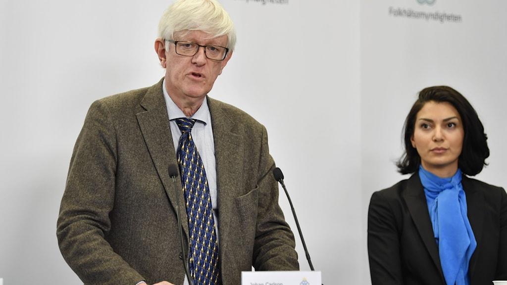En man med kavaj och slips står framför en mikrofon, till höger står en kvinna med blå blus.