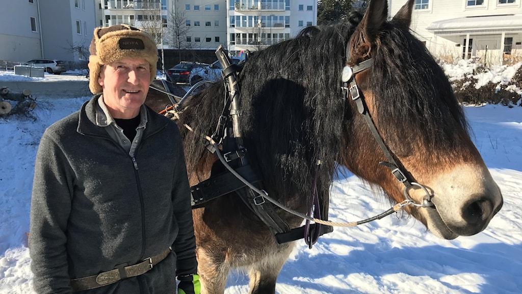 Tom Meurling, naturvårdare i Sollentuna står med hästkollegan Karlsson i snön.
